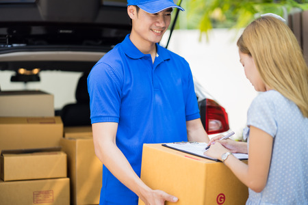 cardbox: Asian woman receiving a package at home from a delivery guy