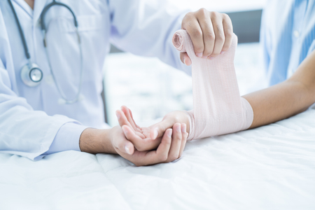 Close-up arts is bandages bovenste ledematen van de patiënt.