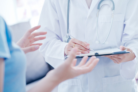 Woman doctor talking to her male patient at office Standard-Bild