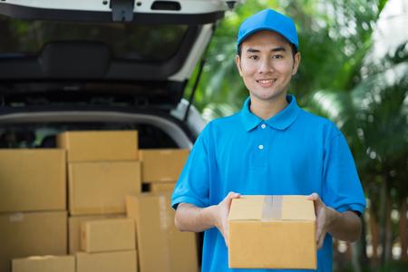 패키지를 들고 파란색 제복을 입은 아시아 우체부. 배달 개념 스톡 콘텐츠