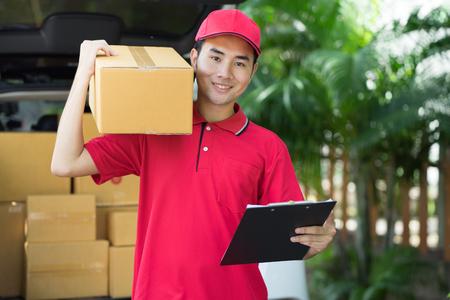 carretilla de mano: Cartero asiático en el uniforme azul que sostiene el paquete. Concepto de entrega