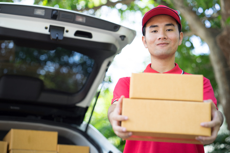 delivery service: Asian Postman in blue uniform holding package. Delivery concept