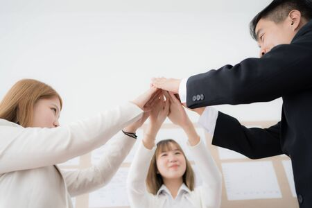 Business people group joining hands and representing concept of friendship and teamwork. Asian people