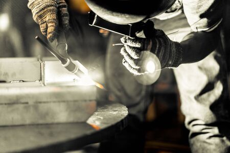 Asian worker making sparks while welding steel