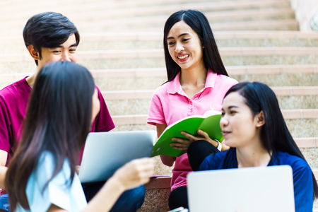Group of happy teen high school asian students sitting on staircase Stock Photo