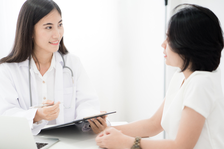 Female doctor consulting patient. Asian people