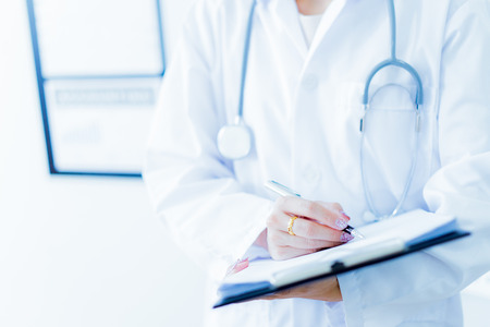 Close-up view of female doctor hands filling patient registration form. Healthcare and medical concept Banque d'images