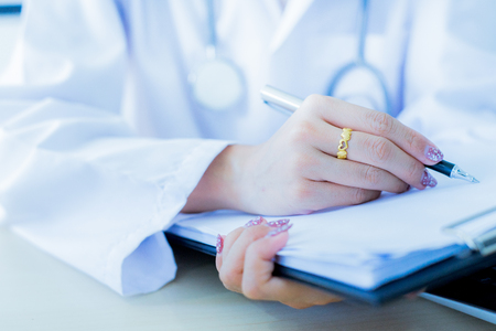 Close-up view of female doctor hands filling patient registration form. Healthcare and medical concept Stock Photo