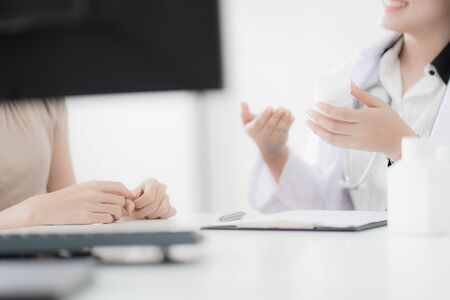 Doctor explaining diagnosis to her female patient. Asian people Stock Photo