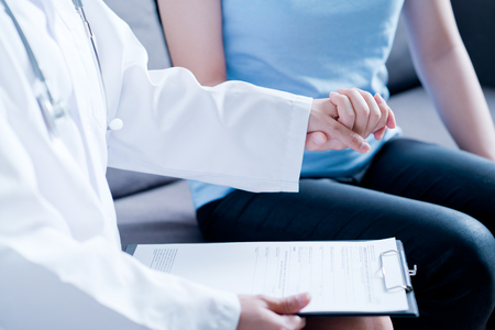 Hand of doctor reassuring her female patient Stock Photo