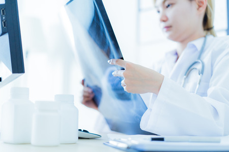 Woman doctor looking at X-Ray Radiography in patients room