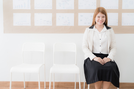 Businesswoman sitting in a row of empty chairs. Asian people