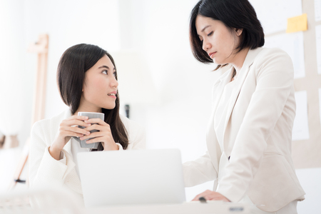 Two Businesswomen talking discussing concept in modern office. Asian people