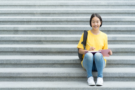 College asian student female sitting on staircase Stock Photo