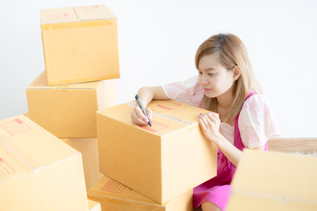 Young Asian woman working online shopping at home office, Packaging and delivery scene Stock Photo