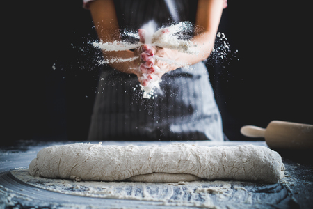 Making dough by female hands at bakery