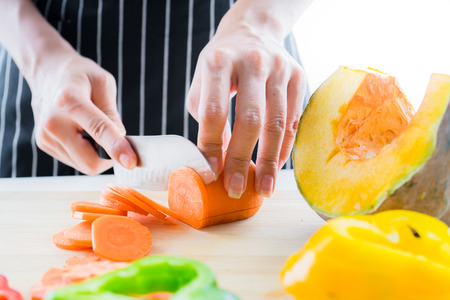 Female hands cutting fresh vegetables for cooking