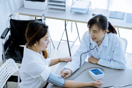 Doctor visiting a patient and checking her blood pressure at the hospital 写真素材 - 121175356