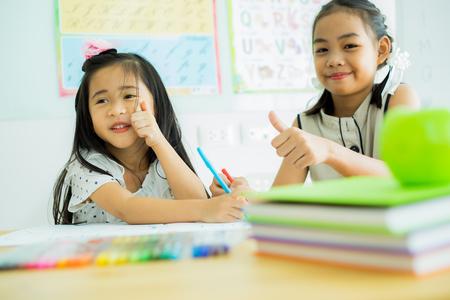 Asiatisches süßes kleines Kindermädchen, das zu Hause zeichnet Standard-Bild