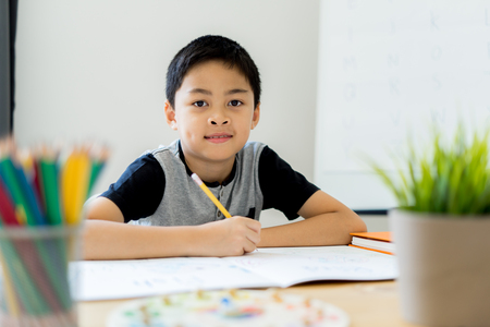 Asian little boy drawing at home. Education concept