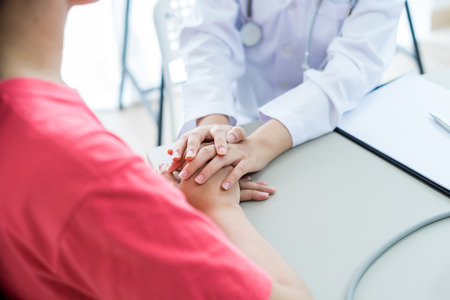 Hand des Arztes, der ihre Patientin beruhigt