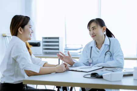 Vrouwelijke arts raadplegende patiënt. Aziatische mensen