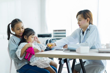 Asian cute girl visiting a doctor. Medicine and children's therapy concept