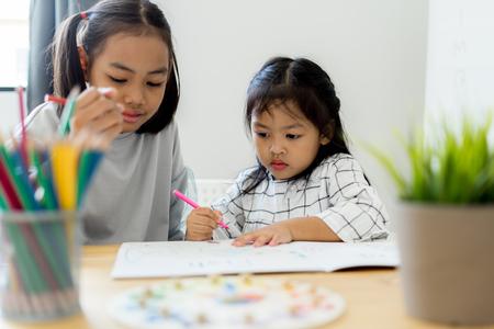 Dibujo de niña niño lindo asiático en casa. Concepto de educación Foto de archivo