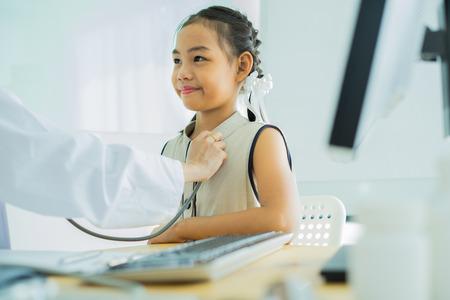 Asiatischer Arzt untersucht ein kleines Mädchen mit einem Stethoskop