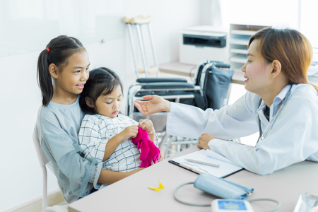 Asian cute girl visiting a doctor. Medicine and childrens therapy concept Stock Photo