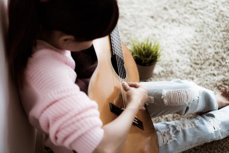 A beautiful asian woman playing acoustic guitar Stock Photo