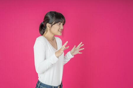 Young asian woman shouting. Shout. Crying emotional  woman screaming on pink studio background. Female half-length portrait. Imagens