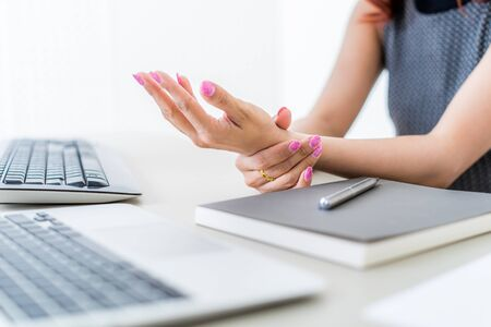 Asian woman holding her wrist pain from using computer. Office syndrome