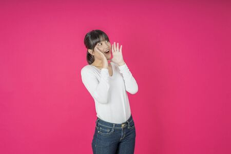 Do not miss. Young asian woman shouting. Shout. Crying emotional  woman screaming on pink studio background. Female half-length portrait. Human emotions, facial expression concept. Trendy Archivio Fotografico