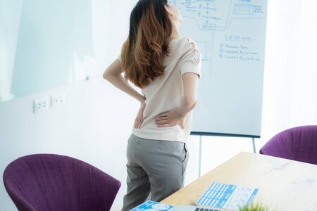 Asian woman with back pain in office Banco de Imagens - 129957799