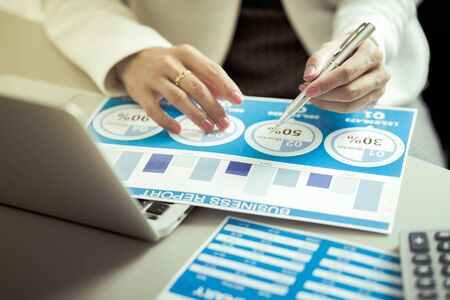 Asian business woman reviewing data in financial charts and graphs. Accounting Banco de Imagens - 129959662