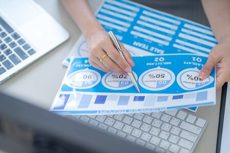 Asian business woman reviewing data in financial charts and graphs. Accounting Banco de Imagens - 129959667