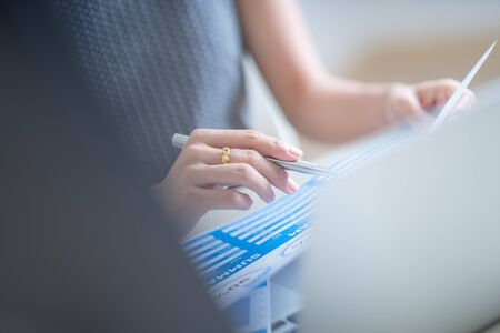 Asian business woman reviewing data in financial charts and graphs. Accounting Banco de Imagens - 129960025
