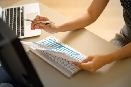Asian business woman reviewing data in financial charts and graphs. Accounting Banco de Imagens - 129960030
