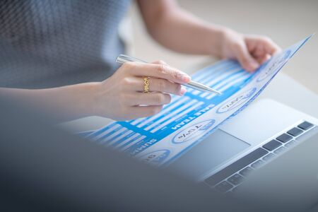 Asian business woman reviewing data in financial charts and graphs. Accounting Banco de Imagens - 129960029