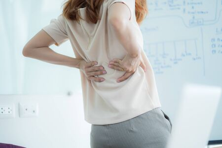 Asian woman with back pain in office Banco de Imagens - 129960200