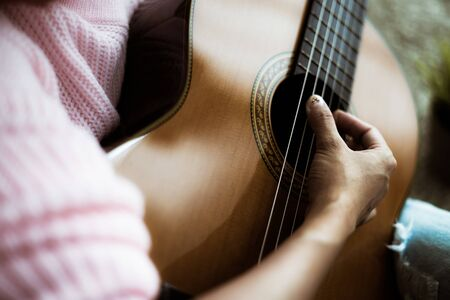 A beautiful asian woman playing acoustic guitar Banco de Imagens