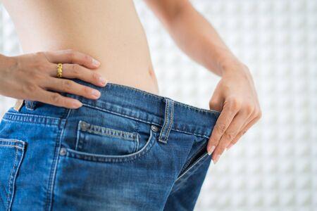 Slim female wearing oversized pants, diet concept