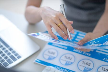 Asian business woman reviewing data in financial charts and graphs. Accounting Banco de Imagens - 129963560