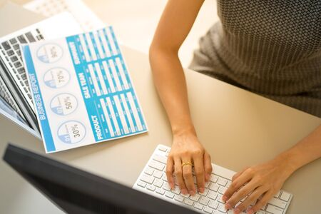 Asian business woman reviewing data in financial charts and graphs. Accounting Banco de Imagens - 129963598