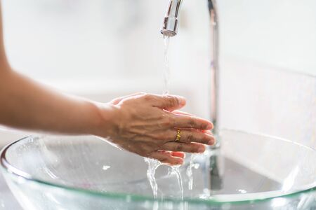 Washing hands with soap under the faucet with water Banco de Imagens