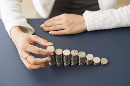 Asian women put coin stack money for money growth concept