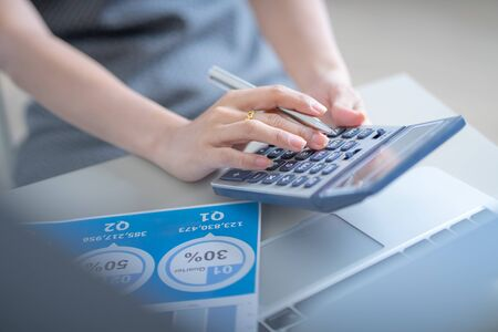 Asian business woman reviewing data in financial charts and graphs. Accounting Banco de Imagens - 129963906