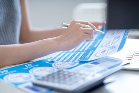 Asian business woman reviewing data in financial charts and graphs. Accounting Banco de Imagens - 129963976
