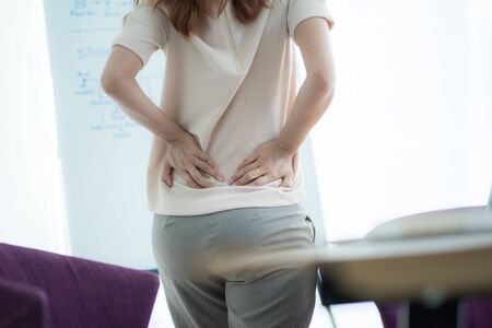 Asian woman with back pain in office Banco de Imagens - 129963985